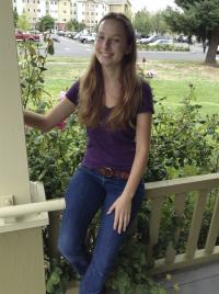 Girl smiling sitting on porch railing holding beam