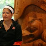 Female student sitting next to Native American carvings